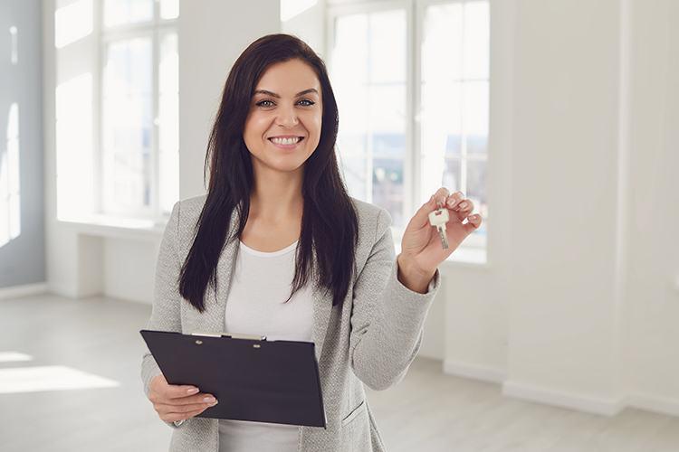 Female Realtor agent holding a key